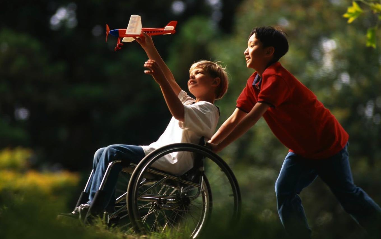Criança cadeirante brinca ao ar livre.